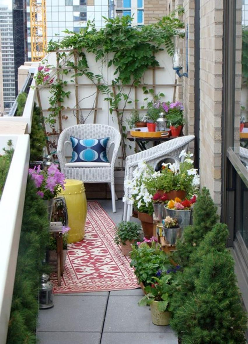The outdoor rug and white wicker furniture are the center of attention on this balcony.